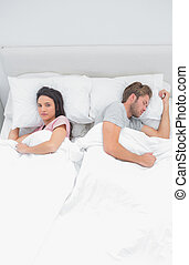 Woman looking at camera while next to her sleeping partner