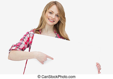 Woman looking at camera while showing a blank board