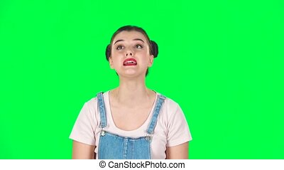 Woman looking at camera with anticipation, then very upset against green screen. Slow motion