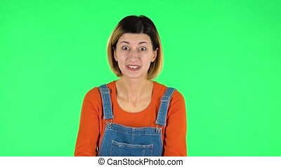 Woman looking at camera with anticipation, then very upset. Green screen