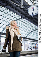 Woman looking at clock in train station as her train has a delay