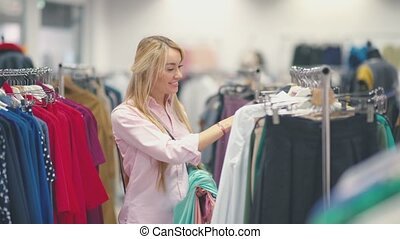 Woman looking at clothes on rail in clothing store. Attractive young woman shopping