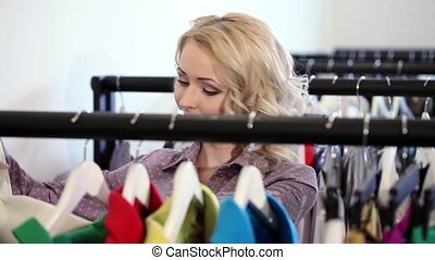 Woman looking at clothes on rail in store - Woman looking at...