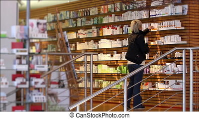 Woman looking at cosmetics in supermarket.