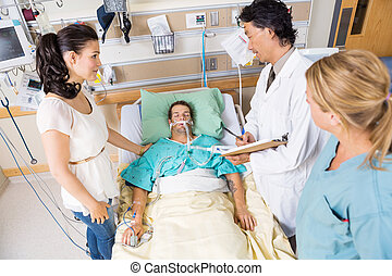 Woman Looking At Doctor Examining Patient - High angle view...