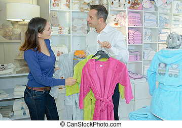 Woman looking at dressing gowns in store