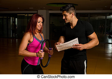 Woman looking at exercise charts with fitness trainer
