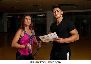 Woman looking at exercise charts with personal trainer