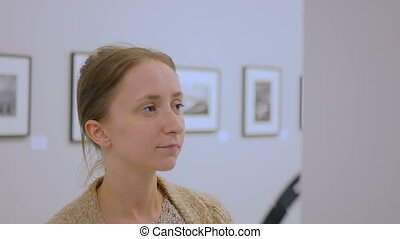 Woman looking at exposition and listening audio guide in...