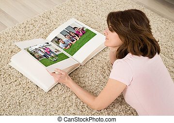 Woman Looking At Family Photo Album