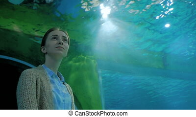 Woman looking at fish in large public aquarium tank at...