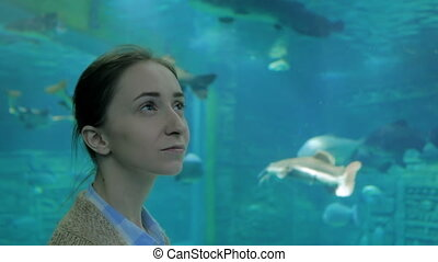 Woman looking at fish vortex in large public aquarium tank...