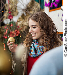 Woman Looking At Golden Bauble In Store