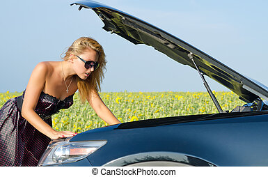 Woman looking at her car engine