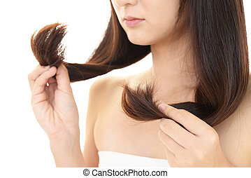 Woman looking at her damaged hair