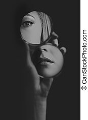Woman looking at her eye and mouth in small mirror artistic conversion