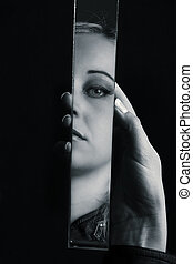 Woman looking at her face in a shard of broken mirror artistic conversion