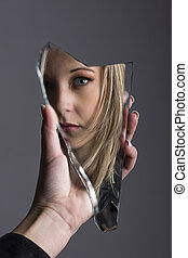 Woman looking at her face in shard of broken mirror