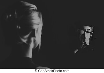 Woman looking at her face in shards of broken mirror artistic conversion
