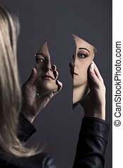 Woman looking at her face in two shards of broken mirror