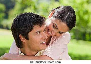 Woman looking at her friend while he is carrying her