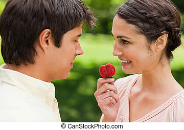 Woman looking at her friend while holding a strawberry