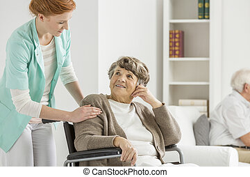 Woman looking at her nurse - Woman on wheelchair looking at...