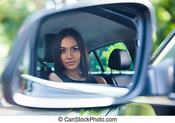 Woman looking at her reflection in a car mirror