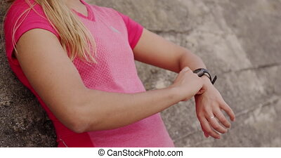 Woman looking at her watch against a wall