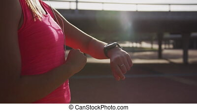 Woman looking at her watch in a park