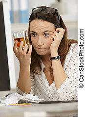 woman looking at her whisky glass while working