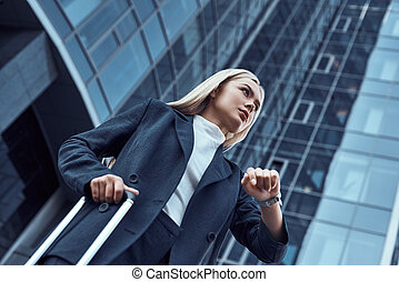 Woman looking at her wrist watch while going to office checking