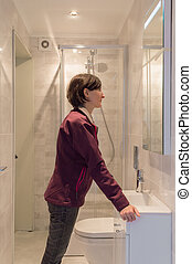 Woman looking at herself in the mirror in a bathroom