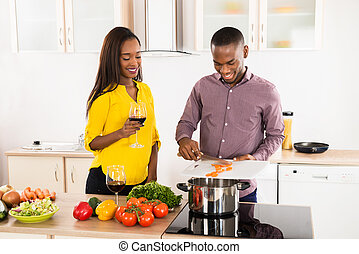 Woman Looking At Husband Preparing Food