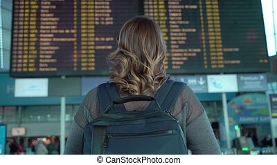 Woman looking at information board in airport