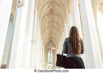 Woman looking at interior of cathedral