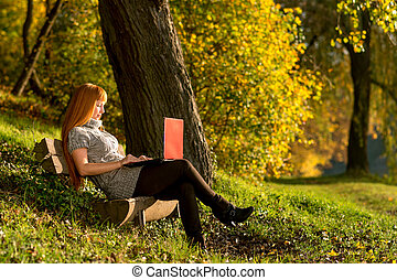 Woman looking at laptop in the quiet autumn forest