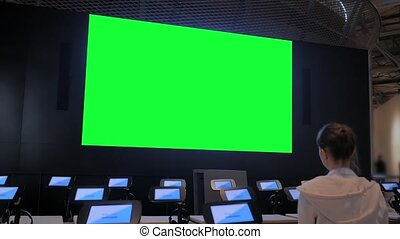 Woman looking at large blank green screen - chroma key concept