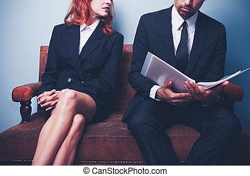 Woman looking at man reading company report