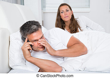 Woman Looking At Man Talking On Mobile Phone