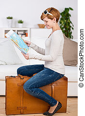 Woman Looking At Map While Sitting On Suitcase