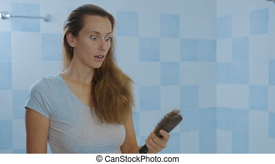 Woman looking at mirror, brushing hair. Irritated young girl dissatisfied with damaged dry hair condition, hair loss