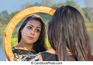 Woman looking at mirror in nature