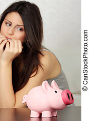 Woman looking at piggy bank