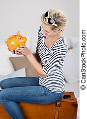 Woman Looking At Piggybank While Sitting On Suitcase In Bed