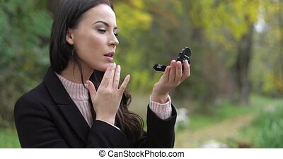 Woman looking at pocket mirror - Beautiful woman in black...