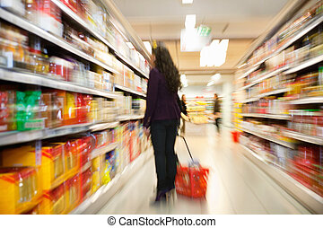 Woman looking at products in shopping store - Blurred view ...