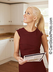 Woman Looking At Property Details In New Home