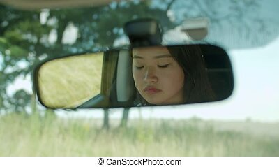 Woman looking at reflection in car rearview mirror