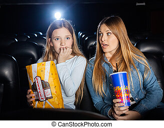 Woman Looking At Scared Daughter Watching Movie